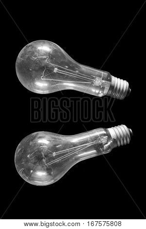 Two old incandescent bulbs covered with dust on a black background