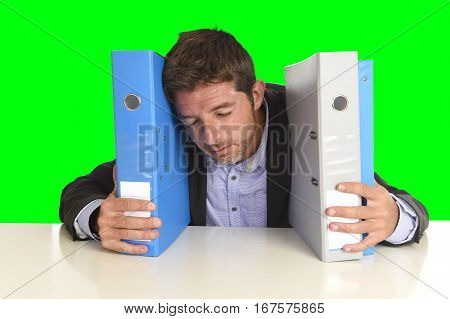 young attractive busy businessman overwhelmed suffering crazy stress at office exhausted holding paperwork folders napping on desk isolated on green chroma key screen background