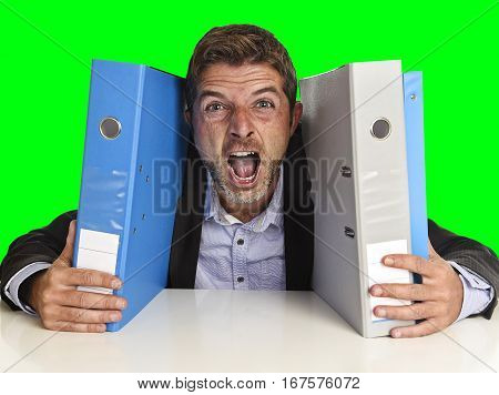 young attractive busy businessman overwhelmed suffering crazy stress at office exhausted holding paperwork folders tired screaming on desk isolated on green chroma key screen background