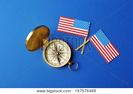 Two USA flags and compass on blue background. Columbus Day concept