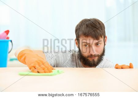 Funny young man wiping furniture with napkin at home