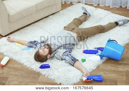 Funny young man tired of cleaning carpet at home