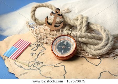 USA flag, rope and compass on old map. Columbus Day concept