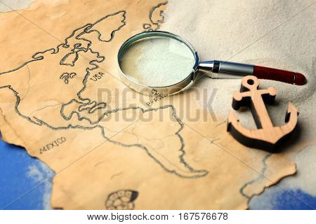 Magnifier and wooden anchor on old map. Columbus Day concept