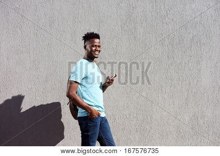 Smiling Man Walking With Bag And Mobile Phone