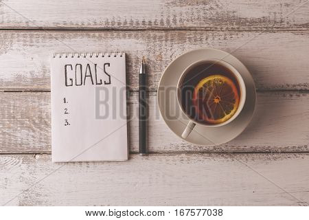 Goals concept. Notebook with goals list, cup of tea on wooden table. Motivation strategy write idea success solution concept. Top view. Retro toned image.