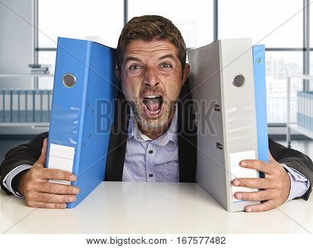 young attractive busy businessman overwhelmed suffering crazy stress at office screaming desperate holding paperwork folders on desk in business frustration and overwork problem