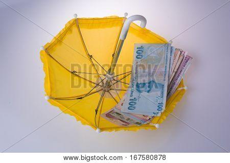 Turkish Lira Banknotes Placed On An Umbrella
