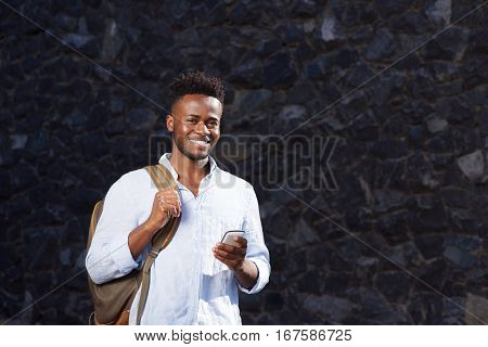 Smiling Man With Bag And Cellphone Standing By Stone Wall