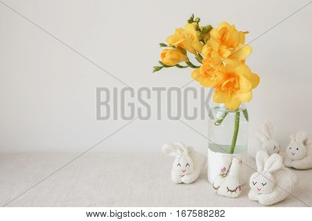 Easter Bunny Rabbits And Yellow Freesia Flowers In Vase On White Linen Table