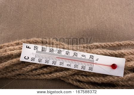 Thermometer On A Brown Rope On A Fabric Background