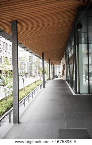 In this picture we can clearly see a modern and elegant corridor with a wooden ceiling design which makes it look more attractive. Few plants , buildings and some people are also seen in this picture.