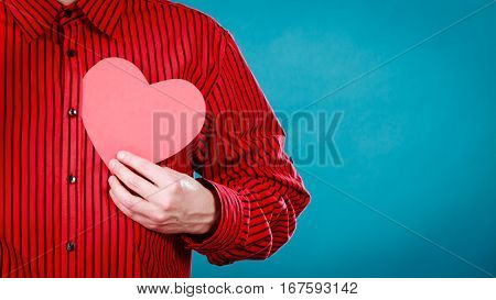 Love hope and help concept. Man holding beautiful red heart in hands. Part body of charity volunteer.