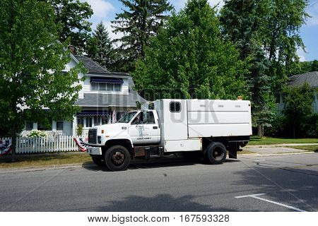 HARBOR SPRINGS, MICHIGAN / UNITED STATES -AUGUST 4, 2016: A white GMC truck belonging to Timberwolf Tree Care is parked on Third Street in Harbor Springs.