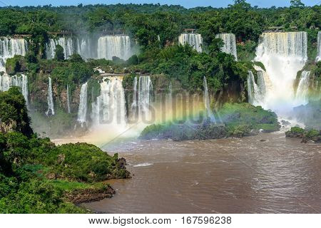 Aerial view of waterfalls cascade of Iguazu Falls with extensive tropical forest and beautiful rainbow in Iguacu National Park, UNESCO World Heritage Site, Foz de Iguacu, Parana State, Brazil