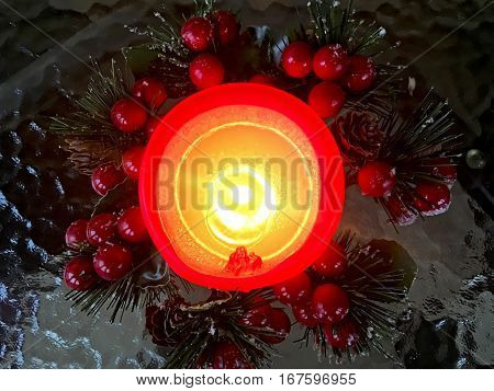 Christmas decoration with candle decorated with viburnum berries cones and pine