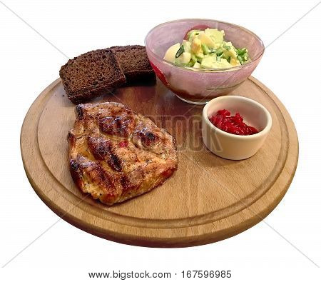 Piece of delicious grilled meat (steak) rests on a round board with a salad of fresh cucumbers eggs and herbs with slices of black bread. Isolated on white background. View from the top