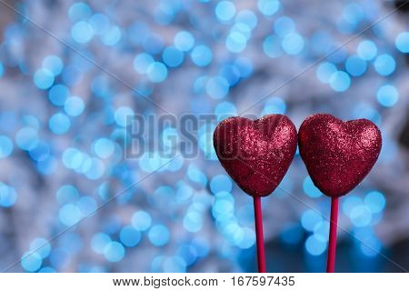 Two red hearts on blue bokeh background