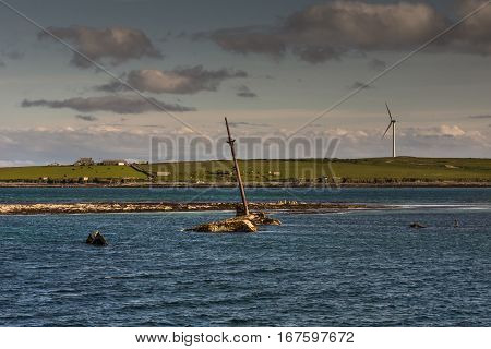 Orkneys Scotland - June 5 2012: The mast and other rusty parts of WW II warship wreck peep out of the sea near Lamb Holm Island. Wind turbine and farms on horizon. Small green band of land splits image in two. Cloudy skies. Blue sea water.