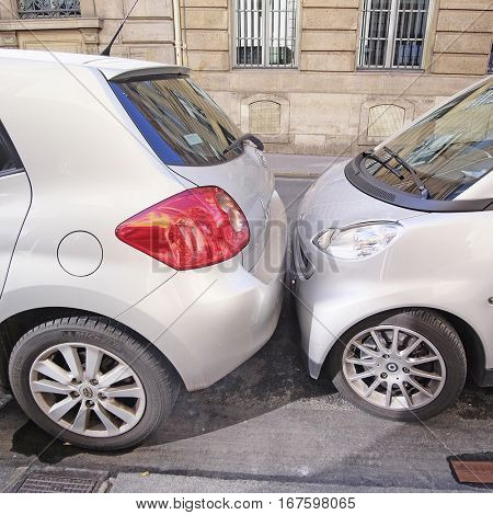 Paris, France, February 9, 2016: cars on a parking in Paris, France. In Paris it is normal to park the cars skin to skin
