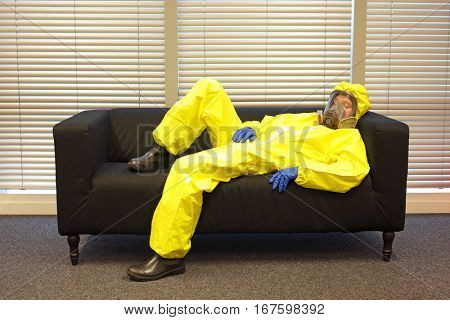 professional in protective clothing, mask and gloves, lying and relaxing on the couch at home in office