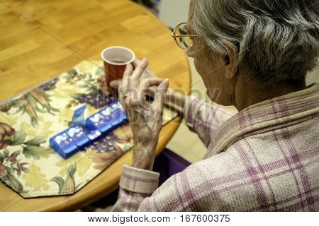 elderly woman taking her medication at kitchen table