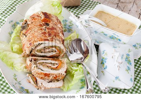 Turkey roll on plate served with vegetables sauce.