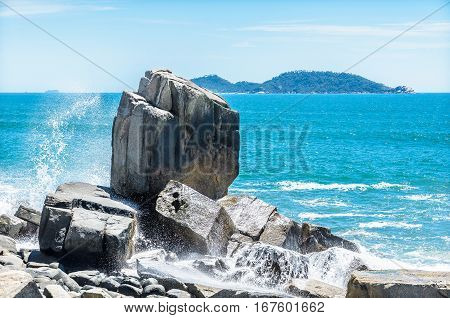 Huge stone by the sea. Sea water hitting the rocks and splashing water on a beautiful day. Morro das Pedras Florianopolis Brazil.