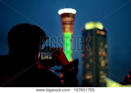 Men use camera to shoot the tower at the Kobe Harbour Land with lights bokeh background Defocused background.