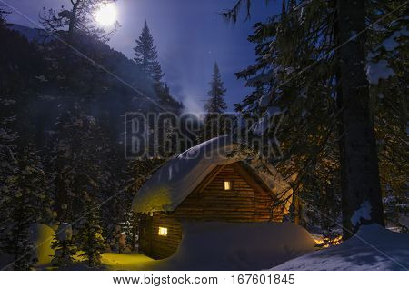Winter moonlit night, snow and the light from windows of a wooden hut, the smoke from the chimney. Full moon on the hill.