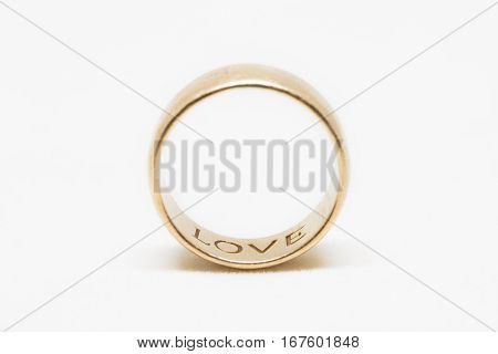 A gold ring with the word love on the inside