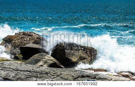 Sea water splashing on the rocks. Waves from a blue ocean hitting the stones of the coast.