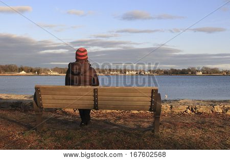 woman on a park bench looking out to the ocean