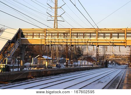 Suburban train station in the snow with footbridge