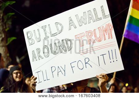 "LONG BEACH, CALIFORNIA - NOVEMBER 12, 2016: Protesters gather with signs at Bixby Knolls Park. Protester holding up sign, ""Build a wall around Trump I'll pay for it !!!"""