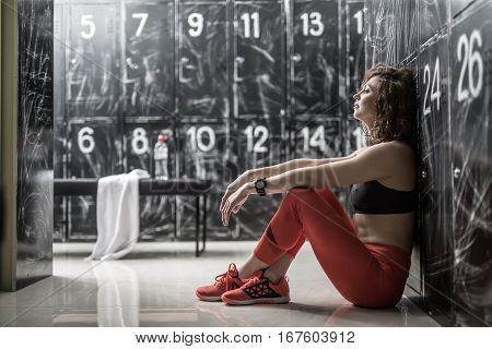 Thoughtful curly woman in red pants and sneakers and black top sits sideways next to the lockers in the dressing-room in the gym. She holds her arms on the knees. Horizontal.