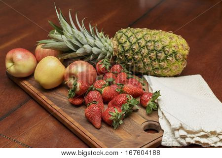a variety of fresh fruit on a wooden cutting board ready to be sliced