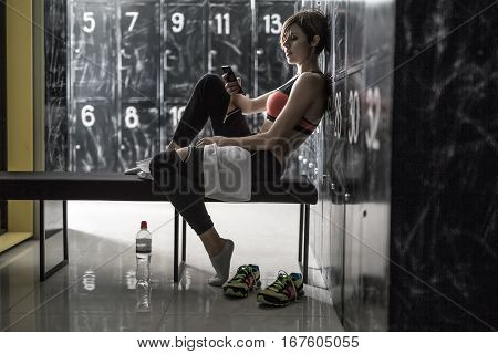 Attractive smiling girl with a mobile phone sits sideways on the bench in the locker-room in the gym. She wears black pants with white socks and a black-pink top. Horizontal.