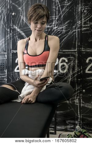 Sexy smiling girl with a mobile phone sits on the bench in the locker-room in the gym. She wears black pants and a black-pink top. She also holds a white towel. Vertical.