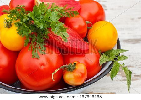 Tomatoes With Green Leaves And Parsley In Metal Bowl In Garden On Sunny Day