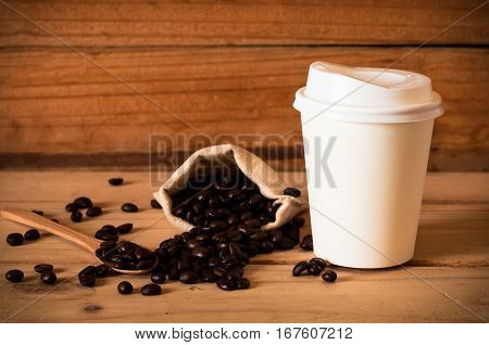 The Coffee Beans And Cup Of Coffee On Wooden Table Background. Still Life Process