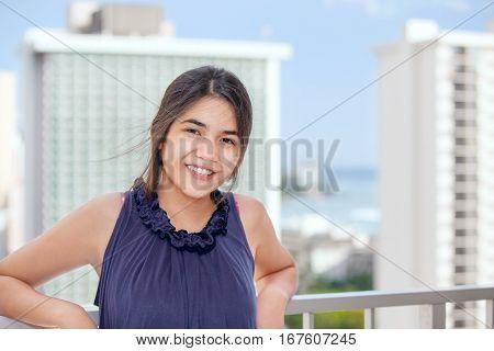 Biracial teen girl standing on outdoor highrise patio happy urban ocean background