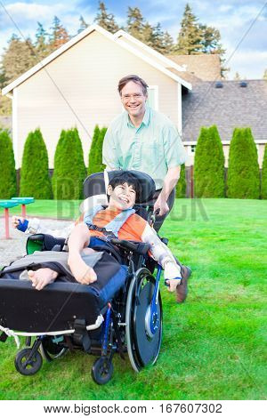 Caucasian father pushing and running with disabled biracial ten year old son in wheelchair outdoors. Child has cerebral palsy.