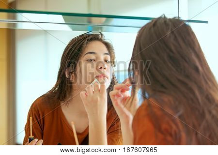 Beautiful biracial Asian Caucasian teen girl putting makeup on while looking in mirror