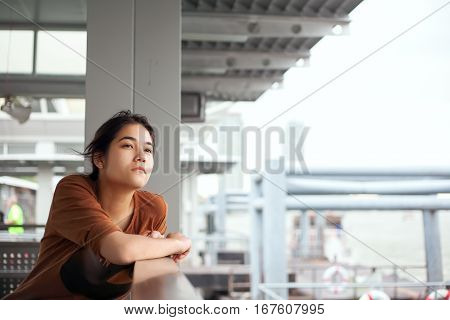 Beautiful biracial teen girl sitting by side of dock looking up thinking with a sad expression