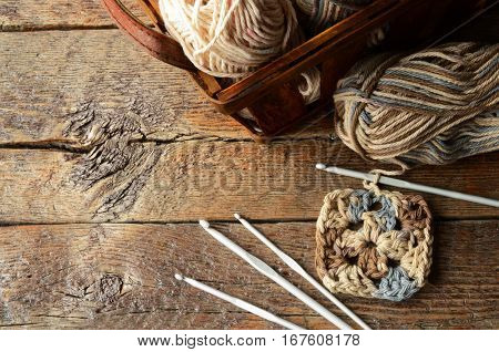 A top view image of a basket of crochet yarn and crochet hook.