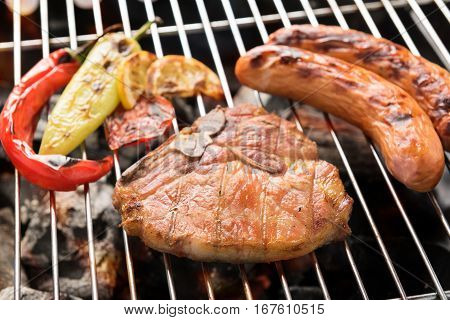 Pork Chop Steak And Vegetable With Sausage On A Flaming Bbq Grill