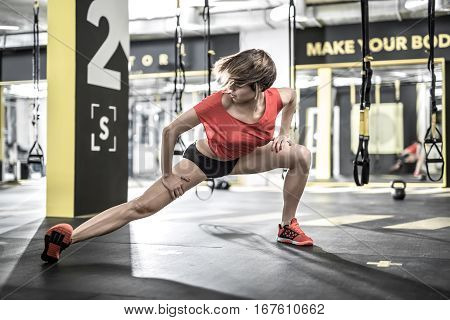 Delightful girl does stretching in the gym on the background of the hanging TRX straps. She wears a red sleeveless and sneakers, black shorts. Horizontal.