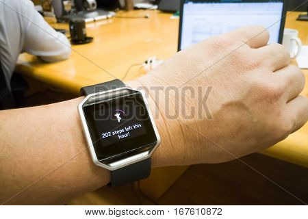 Perspective view of person reading wrist watch with heart and steps tracker in office working poster