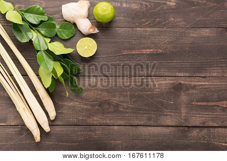Kaffir Lime Leaves, Ginger, Lemon And Green Onions On Wooden Background. Overhead View